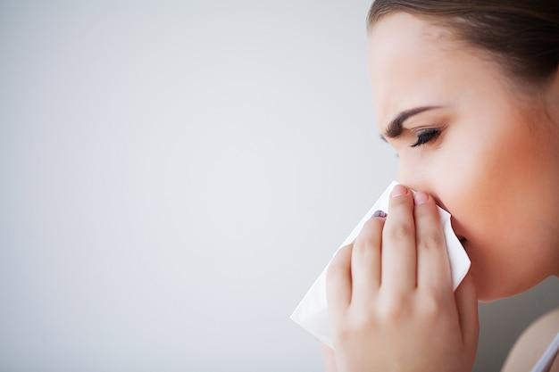 インフルエンザと病気の女性。ペーパーティッシュ、頭の冷たい問題を使用して病気の女性