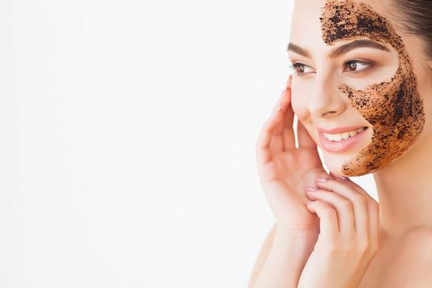顔のスキンケア。魅力的な少女は彼女の顔に黒い炭マスクを作る