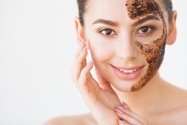 Уход за кожей лица. молодая очаровательная девушка наносит на лицо черную угольную маску