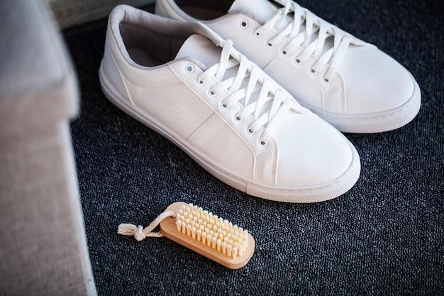 Пара новых стильных белых кроссовок на полу у себя дома.