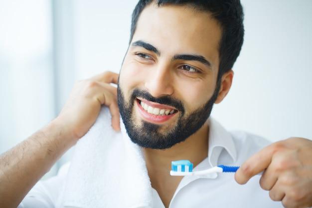 美しい笑顔、歯ブラシで健康的な白い歯を持つ男。