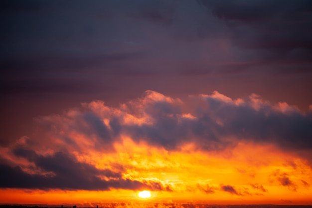 夕暮れ色の空と雲との劇的な夕日。