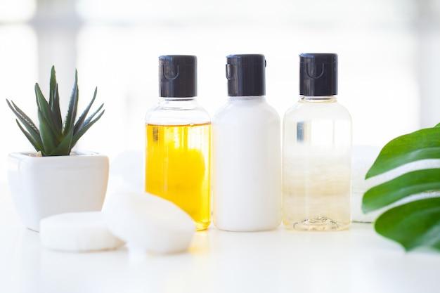 ウェルネス製品と化粧品。ハーブとミネラルのスキンケア。クリーム色の瓶、白い化粧品ボトル。ラベルなし。石鹸と白いタオルのスパセット。