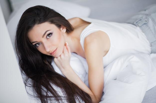 白いベッドでリラックスした笑顔のかなり若いブルネットの女性の肖像画