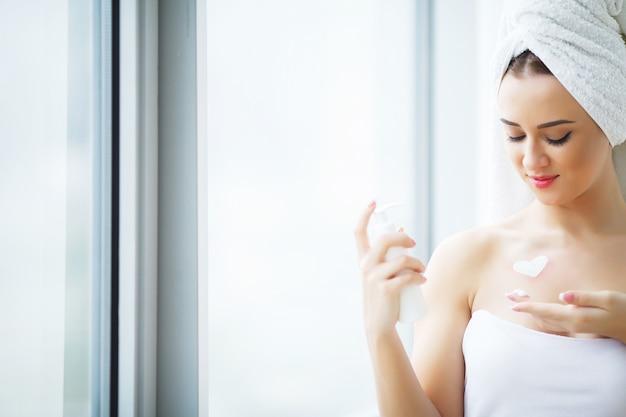 浴室で顔のクリームを適用する完璧な若い女性