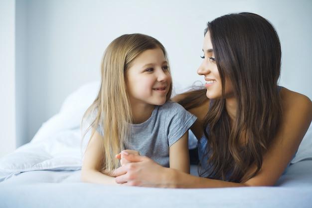 笑顔のベッドで横になっている女性と若い女の子