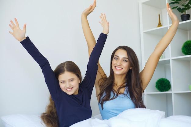 Женщина и молодая девушка лежат в постели