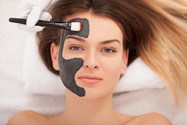 スパのコンセプト。ビューティーサロンで栄養フェイシャルマスクを持つ若い女性をクローズアップ