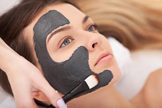 人、美容、スパ、美容、スキンケアコンセプト-目を閉じて横になっている美しい若い女性とスパでブラシで顔のマスクを適用する美容師のクローズアップ