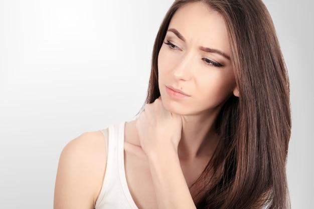 疲れた首。首の痛みに苦しんでいる美しい若い女性。魅力的な女性の疲れ、疲れ、ストレスを感じます。手で痛みを伴う首をマッサージの女の子。体と健康管理のコンセプト。