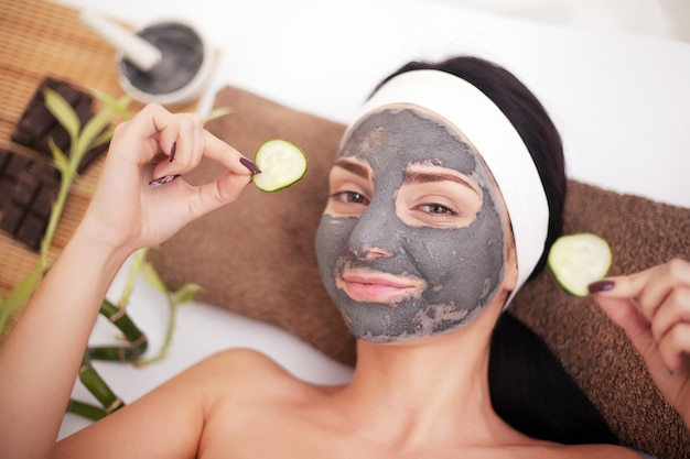 ビューティーサロン、ウェルネスの女性。目のマスクの緩和とキュウリのスライスの化粧品の手順女性の顔