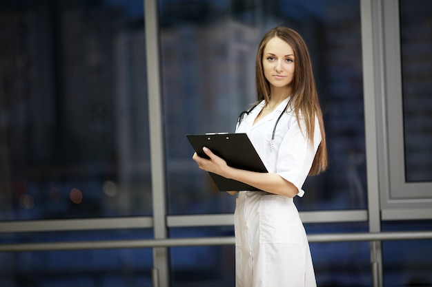医学。女医の笑顔。病院で練習します。かかりつけの医師。若い女性は美しいです。メモを与える