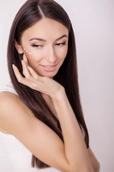 スキンケア。清潔で新鮮な顔に化粧用クリームを持つ若い健康な女性。美しさと健康。フェイシャルビューティートリートメント。