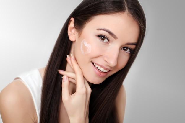 顔に化粧クリームを持つ女性の美しさの顔