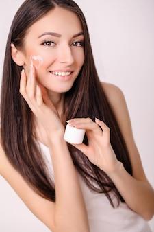 スキンケア。清潔で新鮮な顔に化粧用クリームを持つ若い健康な女性。美しさと健康。