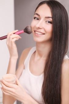 化粧品、健康と美容-目を閉じて化粧ブラシと美しい女性