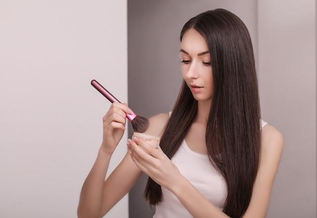 頬にパウダーを適用するミラーを持つ若い女性