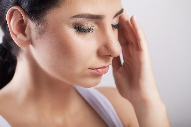 疼痛。健康と痛み。強い緊張の頭痛を持つ疲れの若い女性を強調しました。