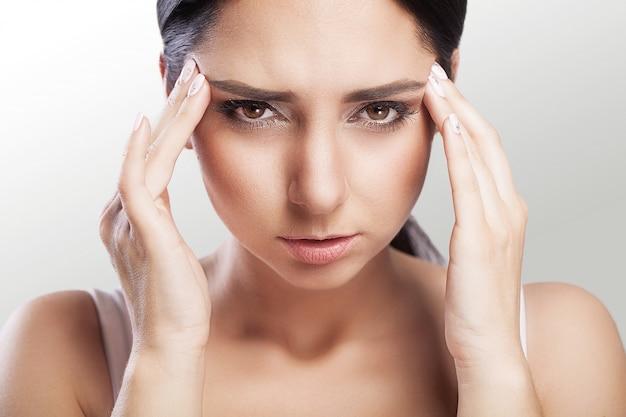 疼痛。落ち込んでいる太りすぎは、深刻な頭痛と頭に触れることで苦しんでいる黒い髪の美しい若い女性です。