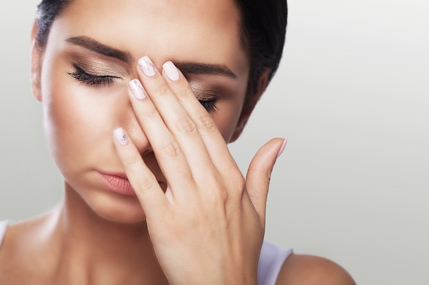 目の痛み強い目の痛みに苦しんでいる美しい不幸な女性。悲しい女性の気持ちのストレスのクローズアップの肖像画。