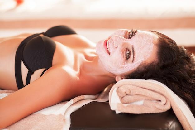 スパマスク。美しい女性は、屋外スパサロンで太陽が降り注ぐビーチでスパマスクを取得します。高品質。シンケア。