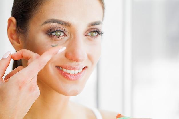 美容と健康。緑の目を持つ美しい少女は、指にコンタクトレンズを保持しています。アイケア。