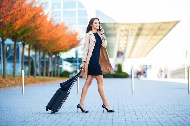 旅行。空港のゲートに行く手荷物を持って歩きながらスマートフォンで話している空港のビジネスウーマン。