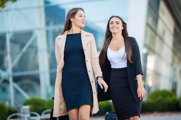 Отпуск. две счастливые девушки путешествуют вместе за границей с чемоданом в аэропорту