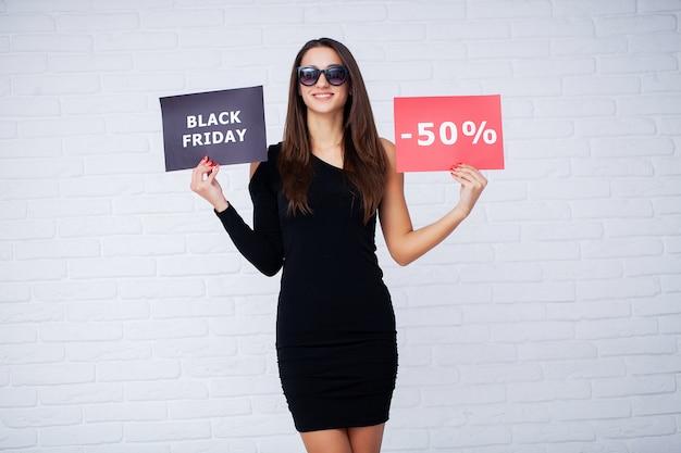 ショッピング。黒い金曜日の休日に割引ブランクを保持している女性
