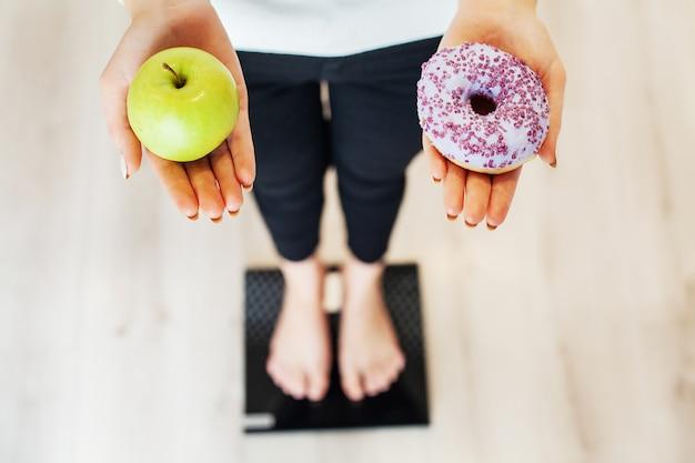 ダイエット。女性は、ドーナツとリンゴを保持している体重計で体重を測定します。お菓子は不健康なジャンクフードです。ファストフード