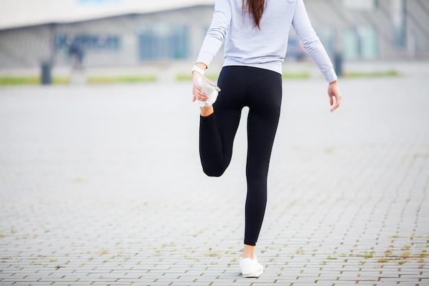 フィットネス。スタジアムでストレッチ運動をしている女性