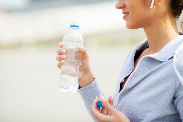 フィットネス。美しい女性は水を飲むと実行した後音楽を聴く