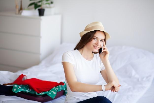 Красивая женщина пакует одежду в чемодане дома.