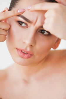 問題のある肌。女性の顔にスポットを粉砕し、鏡で見ています
