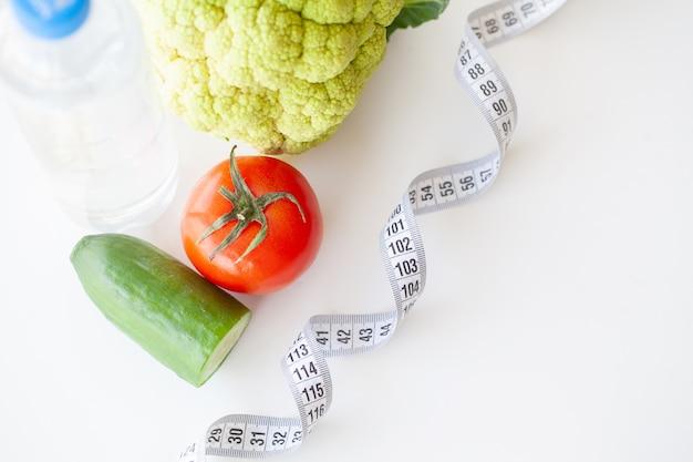 ダイエット。フィットネスと健康食品のダイエットコンセプト。野菜とバランスの取れた食事。新鮮な緑の野菜、測定テープ