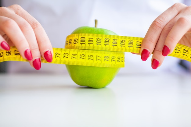 ダイエット。フィットネスと健康食品のダイエットコンセプト。野菜とバランスの取れた食事。青リンゴを測定陽気な医師栄養士の肖像画。自然食品と健康的なライフスタイルのコンセプト。