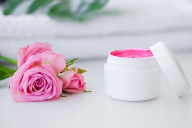 スパ。ウェルネス製品と化粧品。スパリラクゼーション用のタオル、クリーム、ピンクの花。フェイスケア用の天然オーガニック化粧品。バス用品、バスルームセット