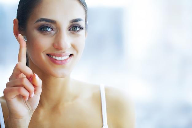 美容と健康。コンタクトレンズと美しい若い女の子。女性は彼女の指に緑のコンタクトレンズを保持しています。ヘルシービュー