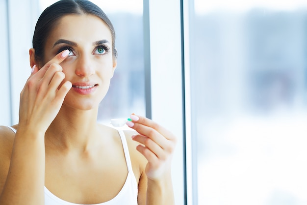 健康。若い女性は目薬を適用します。新鮮なビュー。緑色の目で美しい女性の肖像画。