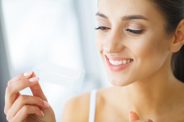 歯のホワイトニング。ホワイトニングストリップを保持している美しい笑顔の女性。