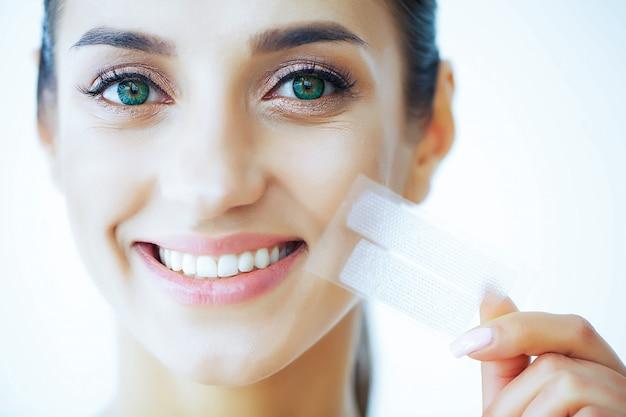 美容と健康。歯のホワイトニングのためのストライプを手で保持している白い歯を持つ美しい少女。美しい笑顔を持つ女性。歯の健康