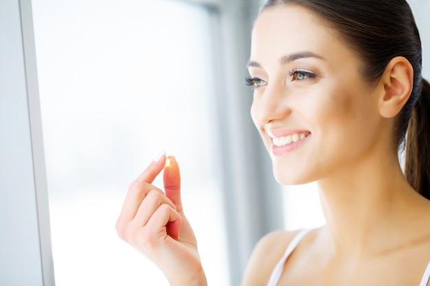 Красивая женщина, держа в руке таблетки рыбьего жира. здоровое питание