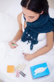 温度計が付いているベッドで病気の女性は高温熱を持っています。