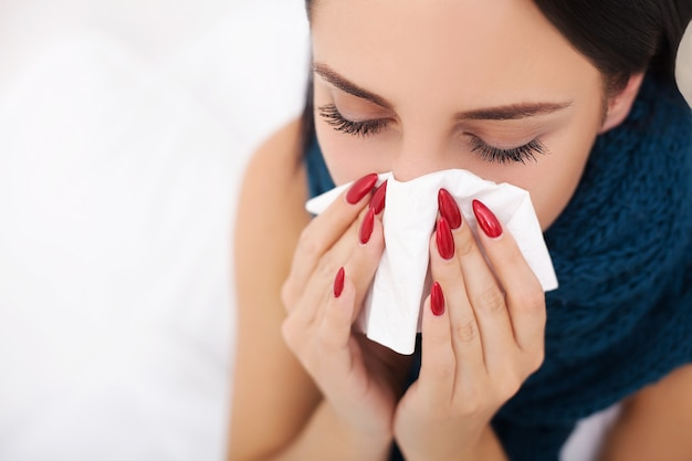 病気の女性とインフルエンザ。女性は風邪をひいた。組織にくしゃみ
