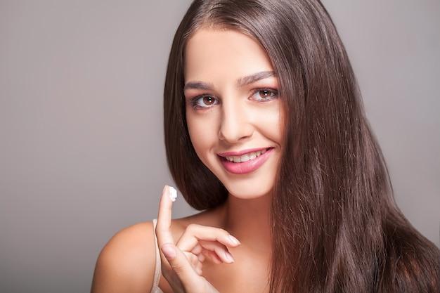 美容スキンケア。新鮮な柔らかい純粋な肌にクリームを入れて美しいセクシーな笑顔の女の子のクローズアップ。頬に美容化粧品を適用するナチュラルメイクを持つ若い女性の肖像画。