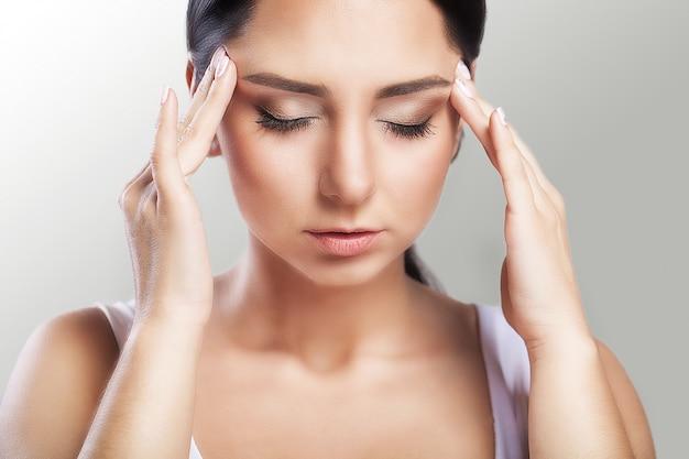 疼痛。美しい女性、ストレス、片頭痛を伴う頭痛、彼女は痛み、大きな肖像画と格闘