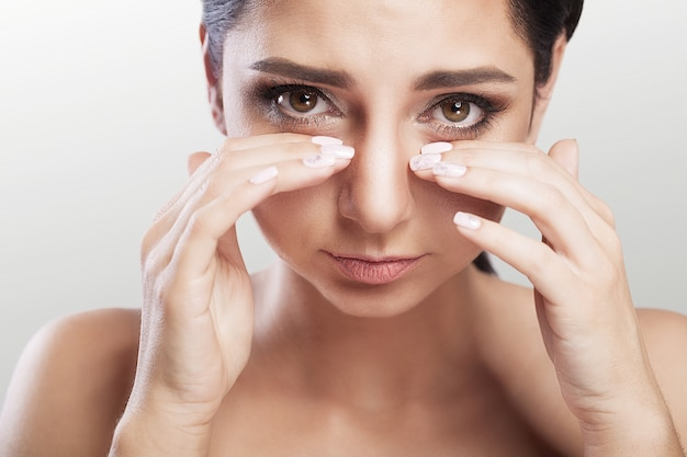 疼痛。目の痛み強い目の痛みに苦しんでいる美しい不幸な女性。手で疲れた痛みを伴う目に触れる悲しいフェミニンな感情ストレスのクローズアップの肖像画。健康管理、医療コンセプト。