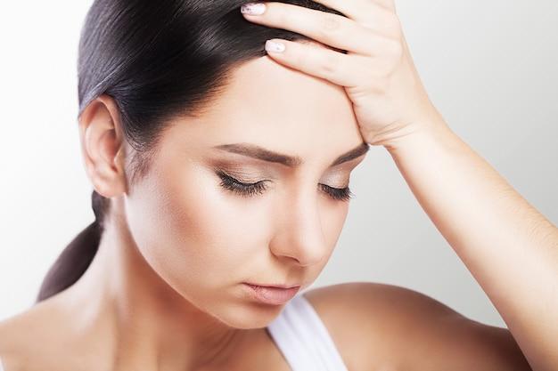 頭痛とストレス。強い頭痛を感じて美しい若い女性。顔の近くに手を繋いでいる痛みを伴う片頭痛に苦しんで疲れてストレス女性の肖像画。医療コンセプト。