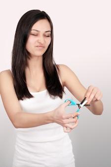 喫煙コンセプトを停止します。若い女性は、幸せな笑みを浮かべてはさみでタバコをカットしました。手、はさみ、タバコに焦点を当てる