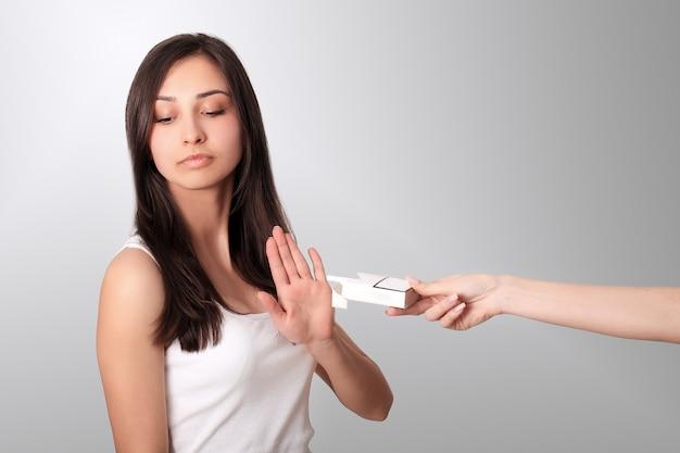Здоровая молодая женщина отказывается принимать сигарету из пачки. портрет красивой девушки показывая знак стопа с рукой к сигаретам. бросить курить концепция.